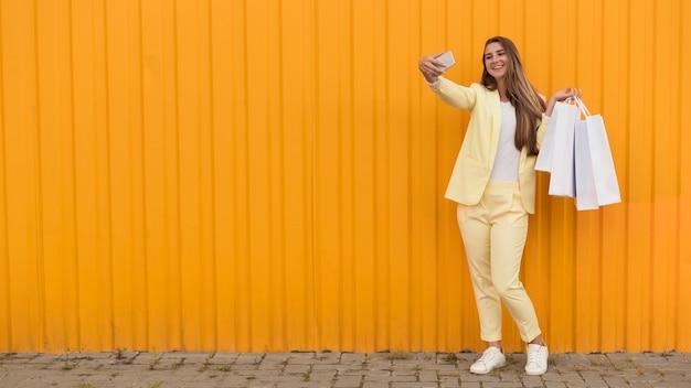 Junger kunde, der gelben kleiderkopierraum trägt