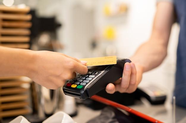 Junger kunde des cafés, das plastikkarte über elektronischem zahlungsautomaten hält, der vom kellner oder vom barista gehalten wird, während für essen oder trinken bezahlt wird