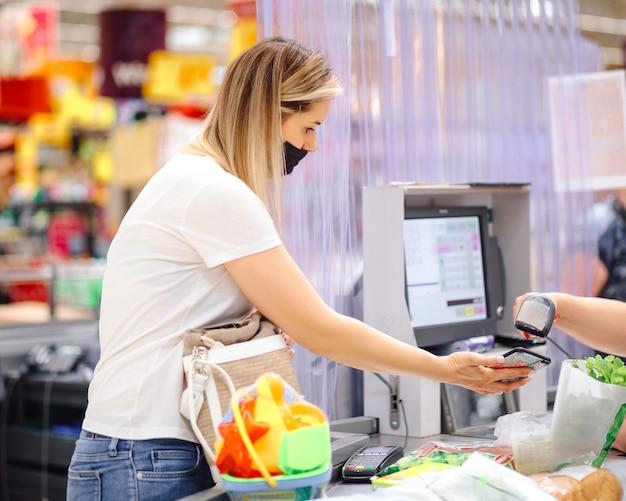 Junger kunde in individueller schutzmaske an der kasse im supermarkt wird mit dem handy berechnet. sicherheitsmaßnahmen und einkaufen. moderne technologien. komfort und kommunikation.