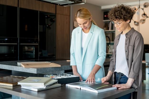 Junger kunde wählt modell oder farbe des möbelstücks im katalog und berät sich mit dem verkäufer