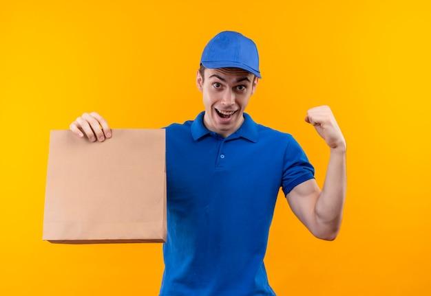 Junger kurier, der blaue uniform und blaue kappe trägt, die glückliche faust tut, hält eine tasche