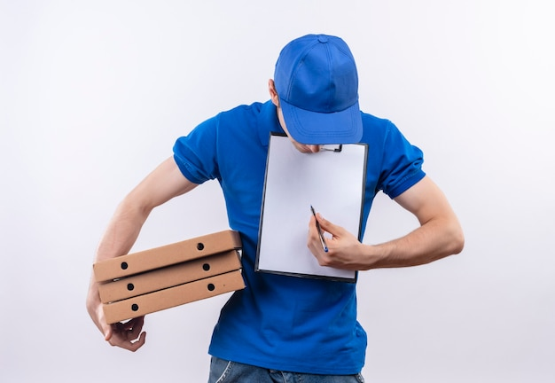 Junger kurier, der blaue uniform und blaue kappe trägt, die kästchen des kopfes unten hält und auf ein klemmbrett schreibt