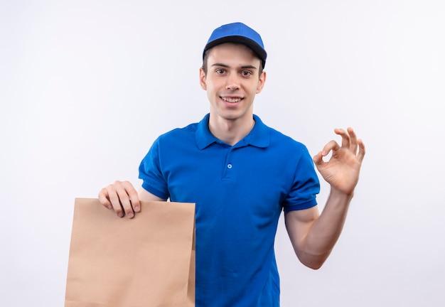 Junger kurier, der blaue uniform und blaue kappe trägt, die mit den fingern gut tut und eine tasche hält