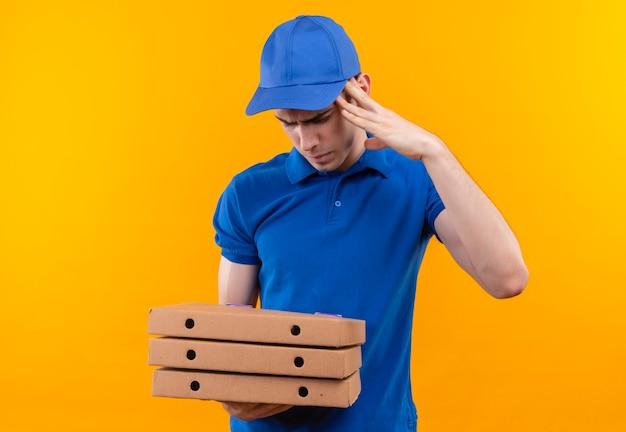 Junger kurier, der blaue uniform und blaue kappe trägt, die verwirrt werden