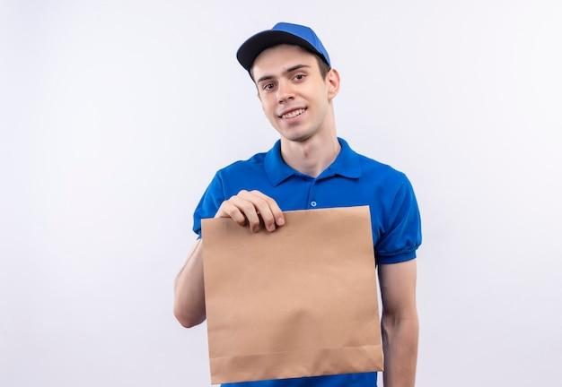 Junger kurier, der blaue uniform und blaue kappe trägt, hält glücklich eine tasche
