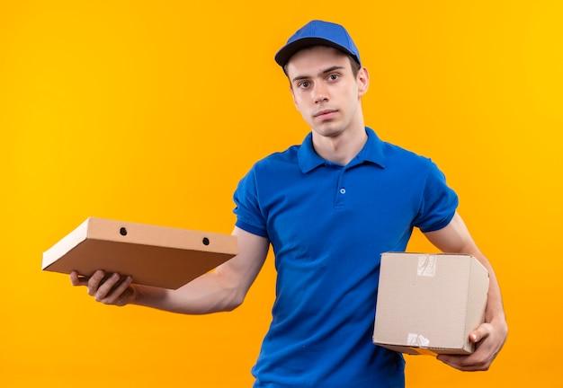 Junger kurier, der blaue uniform und blaue kappe trägt, hält kisten