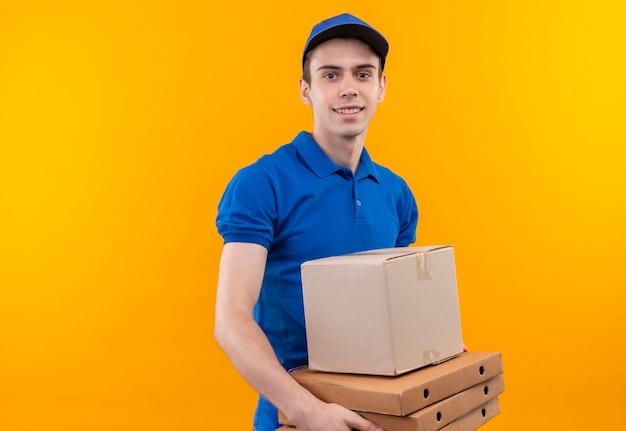 Junger kurier, der blaue uniform und blaue kappe trägt, lächelt und hält schachtel