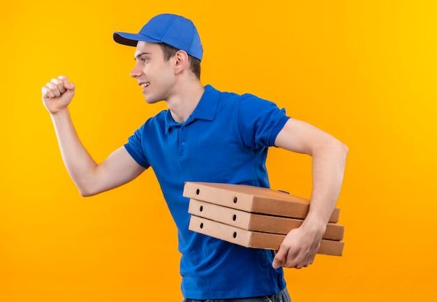 Junger kurier, der blaue uniform und blaue kappe trägt, läuft glücklich mit kisten in den händen