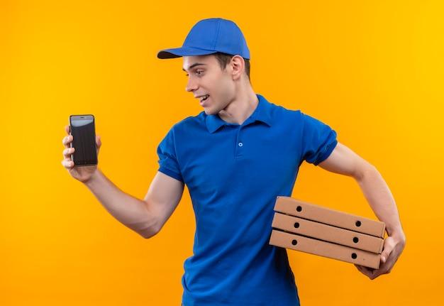 Junger kurier, der blaue uniform und blaue kappe trägt, schaut daneben und hält telefon und kisten
