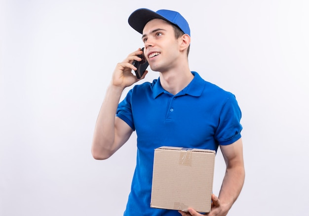 Junger kurier, der blaue uniform und blaue kappe trägt, spricht am telefon und hält eine tasche