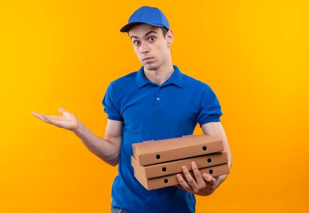 Junger kurier, der blaue uniform und blaue kappe trägt, verwirrtes gesicht tut und kisten hält