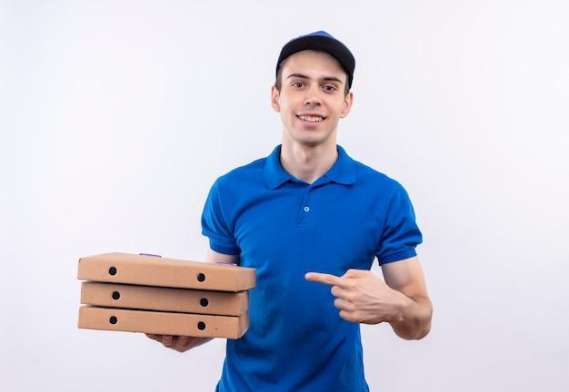 Junger kurier, der blaue uniform und blaue kappenpunkte auf pizzaschachteln mit zeigefinger trägt
