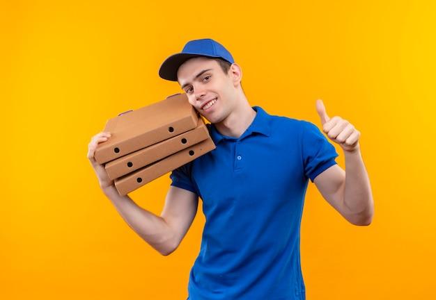 Junger kurier, der blaue uniform und blaue mütze trägt, macht glückliche daumen hoch und umarmt die taschen