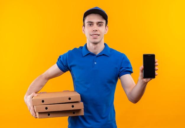 Junger kurier, der blaue uniform und blaues mützenlächeln trägt, hält kisten und telefon