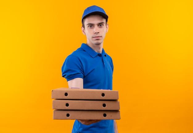 Junger kurier, der blaue uniform und lächelnde blaue kappe trägt, hält kästen