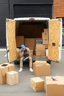 Junger kurier, der mit paketen arbeitet, sitzt im auto und verteilt pakete vor der lieferung