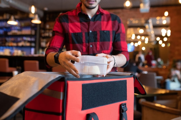 Junger kurier, der plastikbehälter mit gekochtem essen in große offene tasche packt, während er online-bestellungen von kunden sammelt, bevor er sie liefert