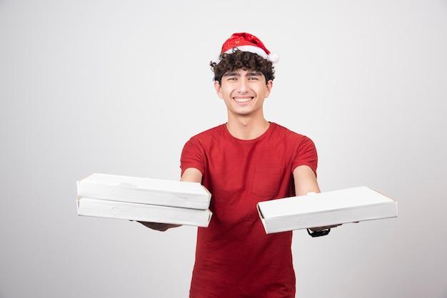 Junger kurier im roten hemd, das pizzakartons gibt.