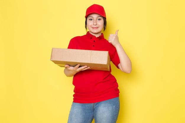 Junger kurier im roten polo rote kappe blaue jeans, die paket lächelnd auf gelb hält
