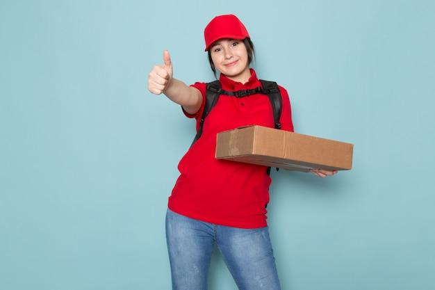 Junger kurier im roten rucksack der roten polo-roten kappe, der paket hält, das auf blau lächelt