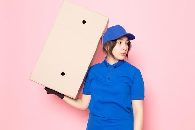 Junger kurier in blauen polo blue cap jeans, die paket auf rosa halten