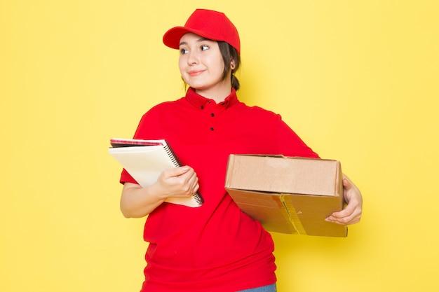 Junger kurier in der roten polo-roten kappe, die paket hält, das auf gelb lächelt