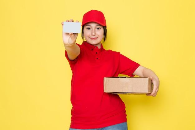 Junger kurier in roter polo-roter kappe, die paket graue karte hält, die auf gelb lächelt