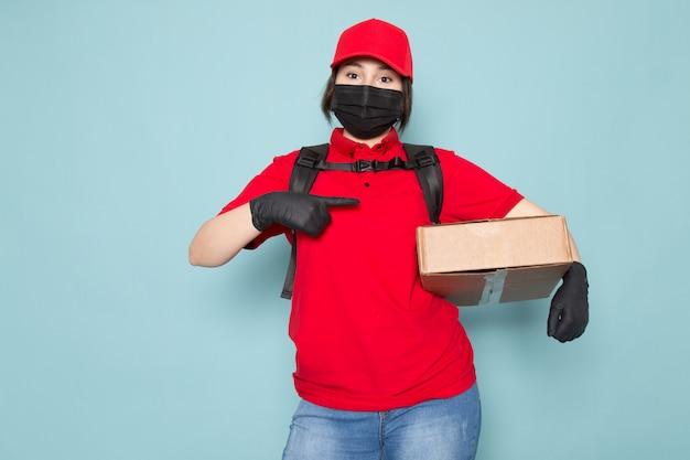 Junger kurier in roter polo-roter kappe schwarze sterile schutzmaske schwarzer rucksack, der paket auf blau hält