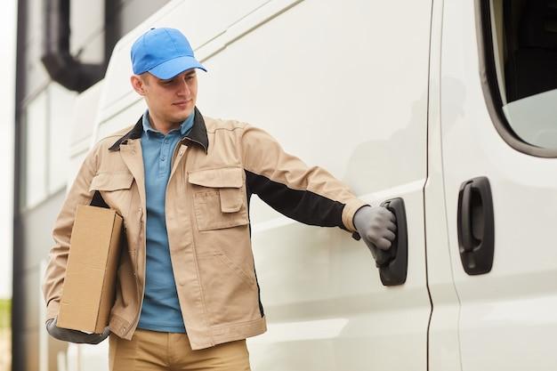 Junger kurier in uniform, der pakete mit dem van ausliefert