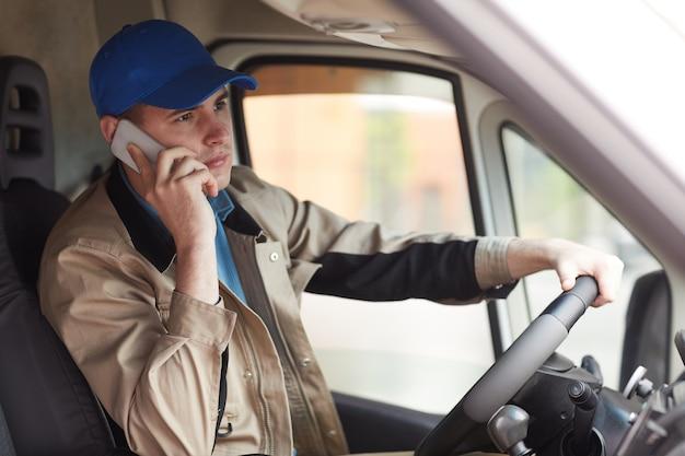 Junger kurier in uniform, der über die lieferung durch das handy berichtet, während er den van fährt