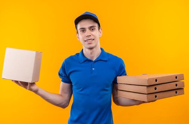 Junger kurier mit blauer uniform und blauer mütze hält eine schachtel auf der linken seite und drei schachteln auf der rechten hand