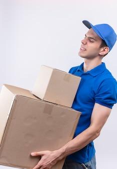 Junger kurier mit blauer uniform und blauer mütze kann keine kisten mehr halten