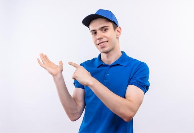 Junger kurier mit blauer uniform und blauer mütze lächelt und zeigt auf seine hand