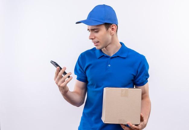 Junger kurier mit blauer uniform und blauer mütze verwirrt und hält eine tasche und ein telefon an den händen