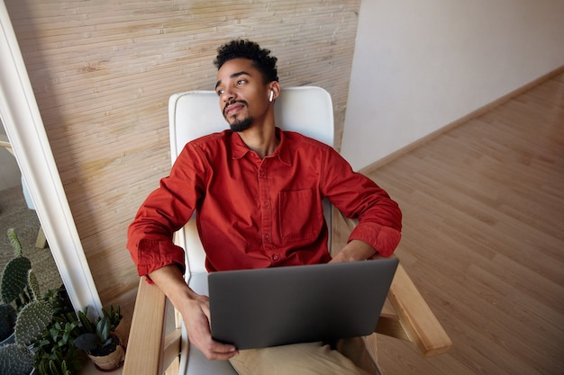 Junger kurzhaariger bärtiger kerl mit dunkler haut, der seinen kopf auf stuhl zurückwirft und fensterblick genießt, während er mit seiner arbeit bricht, auf beigem innenraum sitzend