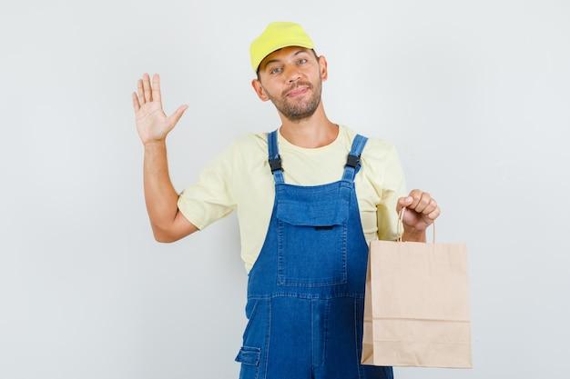 Junger lader, der papiertüte hält und hand in uniform winkt und fröhlich aussieht. vorderansicht.