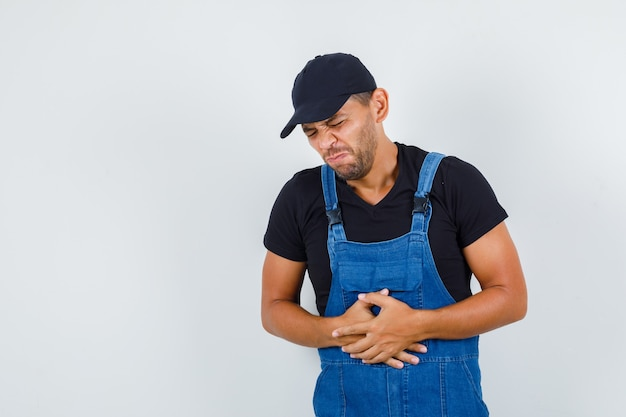 Junger lader, der unter magenschmerzen in der einheitlichen vorderansicht leidet.