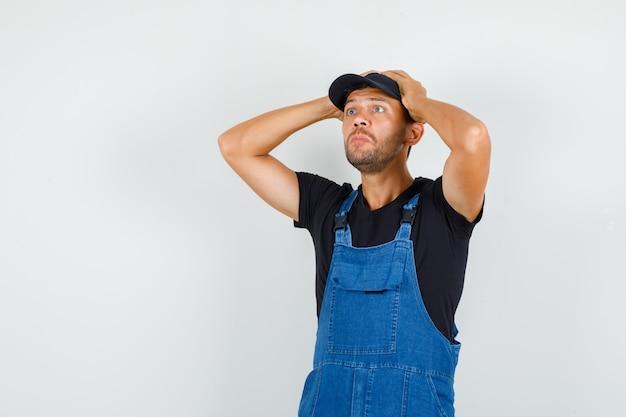 Junger lader in der uniform, die mit den händen auf dem kopf nach oben schaut und verwirrt, vorderansicht schaut.