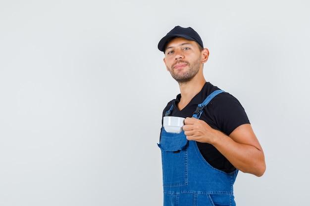 Junger lader in der uniform, die tasse des türkischen kaffees hält, vorderansicht.