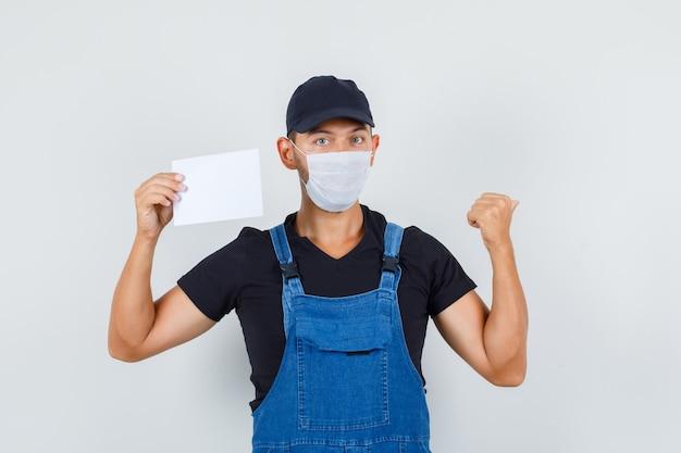 Junger lader in uniform, maske, die papierblatt hält, während zurück zeigt, vorderansicht.