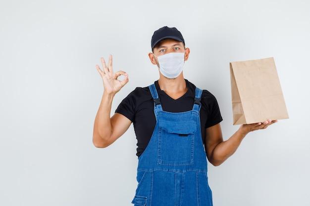 Junger lader in uniform, maske, die papiertüte mit ok-zeichen, vorderansicht hält.