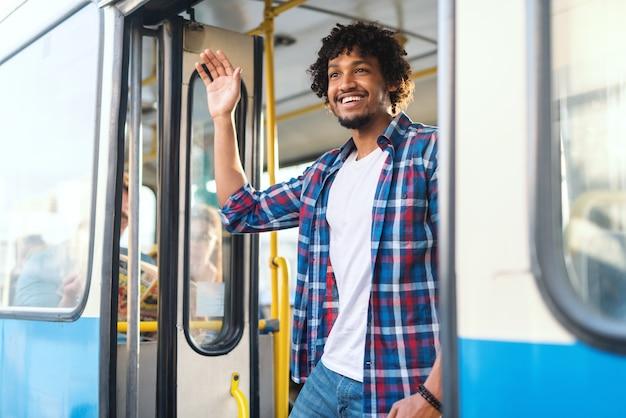 Junger lächelnder afrikanischer kerl, der freundin beim stehen auf der bustür winkt.