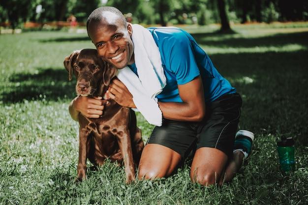 Junger lächelnder afrikanischer mann, der hund umarmt