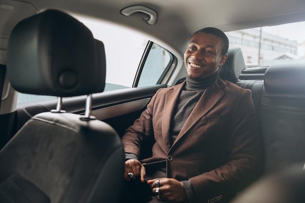Junger lächelnder afrikanischer mann, der smartphone beim sitzen auf rücksitz im auto verwendet.