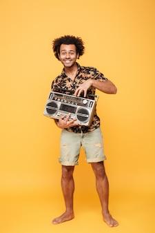 Junger lächelnder afrikanischer mann mit tonbandgerät