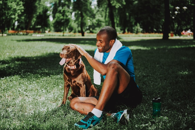 Junger lächelnder afroamerikaner-mann, der hund streichelt.