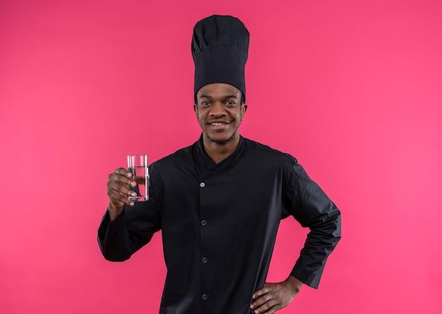 Junger lächelnder afroamerikanischer koch in der kochuniform hält glas wasser lokalisiert auf rosa wand