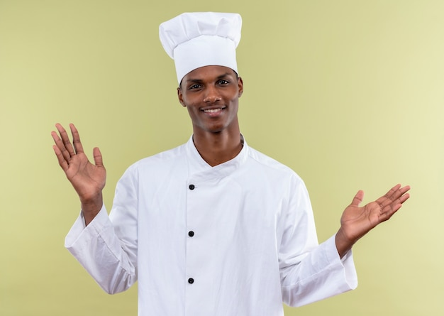 Junger lächelnder afroamerikanischer koch in der kochuniform hält hände offen lokalisiert auf grüner wand