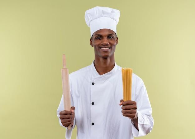 Junger lächelnder afroamerikanischer koch in der kochuniform hält nudelholz und bündel spaghetti in den händen lokalisiert auf grüner wand
