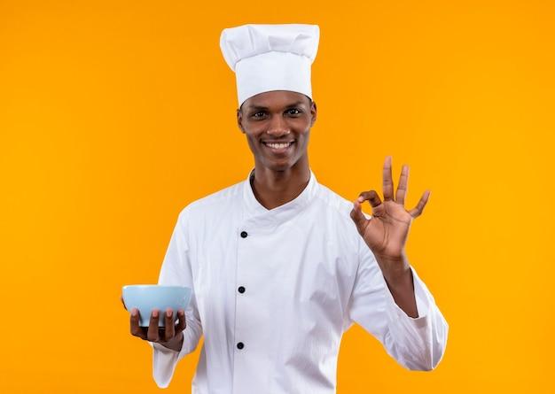 Junger lächelnder afroamerikanischer koch in der kochuniform hält schüssel und gesten ok mit hand lokalisiert auf orange wand